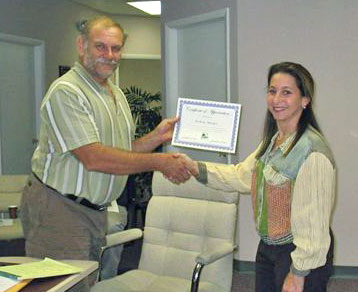 Land Trust Chair Linda Greck presents Founding Chair Nick Maniatis with a certificate honoring his service.